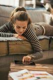 放置在长沙发和使用片剂个人计算机的少妇 免版税库存图片
