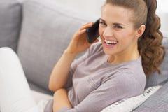 放置在长沙发和谈的手机的微笑的少妇 免版税库存照片