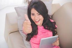 放置在长沙发的妇女使用显示赞许的片剂个人计算机 免版税库存照片