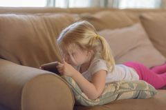 放置在长沙发的小女孩在移动设备的一个展示大字了书写 库存照片