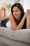 放置在长沙发的愉快的少妇纵向  库存图片