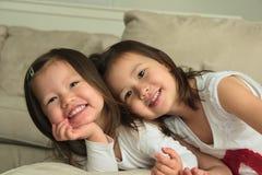 放置在长沙发的胃的微笑的亚裔小孩姐妹 库存图片