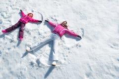 放置在雪的女儿和母亲 库存照片