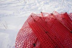 放置在雪的红色净障碍 免版税库存图片