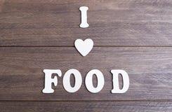 放置在黑暗的木传讯的白色信件我爱食物 免版税库存照片