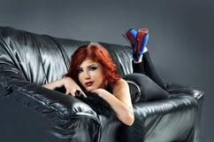 放置在黑皮革长沙发的性感的妇女 库存图片