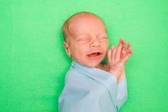 放置在绿色盖子的新出生的婴孩 免版税库存图片