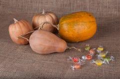 放置在麻袋布的四个南瓜和multycolored甜点 免版税库存图片