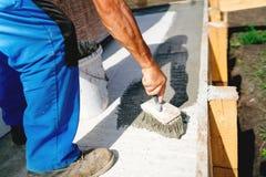 放置密封胶和底漆防水的水泥的建造场所的工作者 免版税库存照片