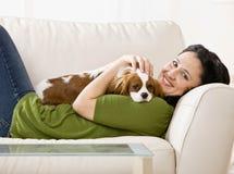 放置小狗妇女的长沙发 免版税图库摄影