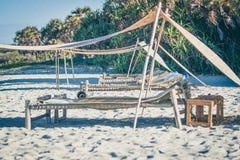 放置床在沙子的海滩 库存图片