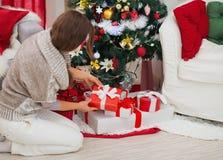 放置当前配件箱的妇女在圣诞树下 免版税库存照片