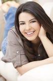 放置微笑的沙发妇女的美丽的讲西班&# 免版税库存图片