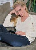 放置性感的片剂妇女年轻人的白肤金发的长沙发 库存图片