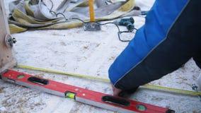 放置户外站点的砖建筑 使用卷尺和建筑水平,一个人测量结构的大小 股票视频
