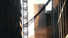 放置户外站点的砖建筑 运转的塔吊 尘土高昂在天空中 在前景的垂悬的导线 股票录像