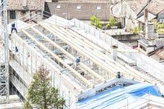 放置户外站点的砖建筑 工作在屋顶sheetin的建筑队 库存照片