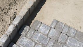 放置新的外部铺路石的配件的过程小心地安置一在一个成水平的和倾斜的土壤基地的位置 图库摄影