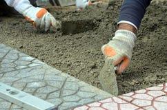 放置新的铺路石的建造者的手小心地安置一在一个成水平的和倾斜的沙子基地的位置 免版税库存照片