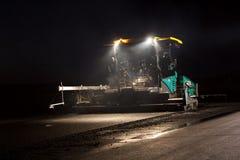 放置新鲜的沥青路面的被跟踪的摊铺机在夜之前 免版税库存图片