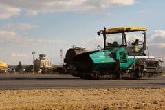 放置新鲜的沥青路面的被跟踪的摊铺机在跑道作为多瑙河三角洲国际机场拓展计划一部分 库存图片