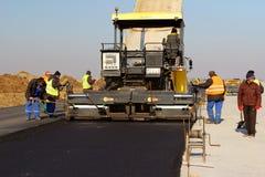 放置新鲜的沥青路面的被跟踪的摊铺机在跑道作为多瑙河三角洲国际机场拓展计划一部分 免版税库存图片