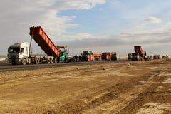 放置新鲜的沥青路面的被跟踪的摊铺机在跑道作为多瑙河三角洲国际机场拓展计划一部分 免版税图库摄影