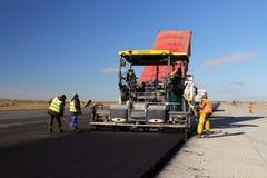 放置新鲜的沥青路面的被跟踪的摊铺机在跑道作为多瑙河三角洲国际机场拓展计划一部分 免版税库存照片