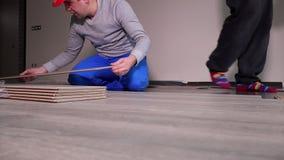 放置木橡木的熟练工在新的屋子里碾压在地板上的委员会 影视素材