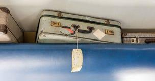 放置机舱行李的-选择聚焦老手提箱 图库摄影