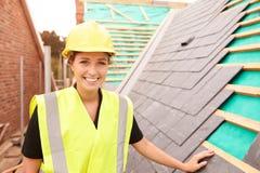 放置板岩瓦片的站点的女性建筑工人 库存照片