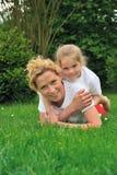 放置母亲年轻人的女儿草 免版税图库摄影