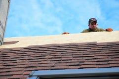 放置沥青木瓦的盖屋顶的人在房子屋顶 有保护绳索的,在安装房子屋顶的上面的安全成套工具,修理盖屋顶的人 免版税库存图片