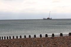 放置海上钻机的缆绳在海滩groynes附近 免版税库存图片
