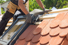放置瓦片的盖屋顶的人的手在屋顶 安装自然红色瓦片使用钳子 有有双重斜坡屋顶的房屋的窗口的屋顶 免版税图库摄影