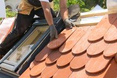 放置瓦片的盖屋顶的人的手在屋顶 安装自然红色瓦片 有有双重斜坡屋顶的房屋的窗口的屋顶 免版税库存照片