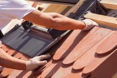 放置瓦片的盖屋顶的人的手在屋顶 安装自然红色瓦片 免版税库存照片