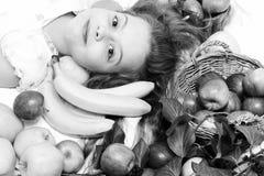 放置用在篮子的五颜六色的果子的逗人喜爱的女婴 免版税库存照片