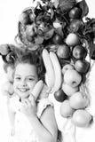 放置用在篮子的五颜六色的果子的逗人喜爱的女婴 免版税图库摄影