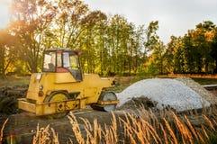 放置的沥青黄色老机器在路早晨在黎明 免版税库存图片
