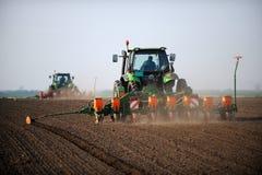 放置种子的拖拉机在领域 免版税库存图片