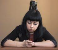放置移动电话的女孩 免版税库存图片