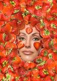 放置纵向草莓在妇女年轻人之下 免版税库存照片