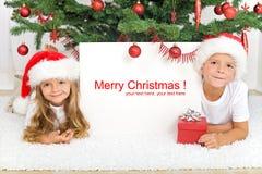 放置结构树的圣诞节孩子下 免版税库存图片