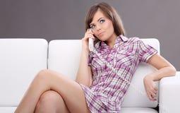 放置联系的电话妇女的长沙发 免版税库存照片