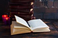 放置象塔的老葡萄酒书在一张黑暗的木桌和一本开放书 红色坚硬盖子,灼烧的烛光焰 库存照片