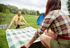 放置野餐毯子的愉快的夫妇在露营地 库存图片
