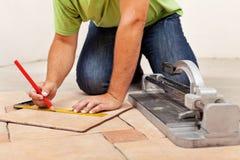 放置陶瓷地垫的工作者手 免版税库存图片