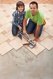 放置陶瓷地垫的父亲和儿子 免版税库存照片