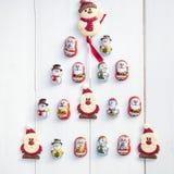 放置以克里斯形式的巧克力圣诞老人,雪人和饼干 免版税库存照片